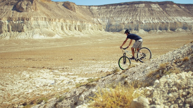 A young man on a bicycle is rolling from the mountain. slow motion