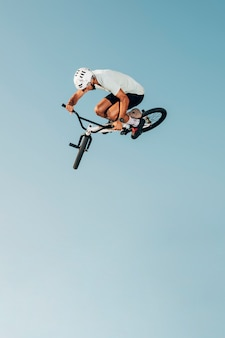 Young man on bicycle jumping low angle view
