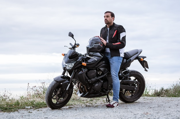Молодой человек байкер со своим черным мотоциклом, готов к вождению, на берегу моря