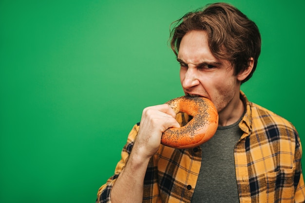 若い男がベーグルを噛む