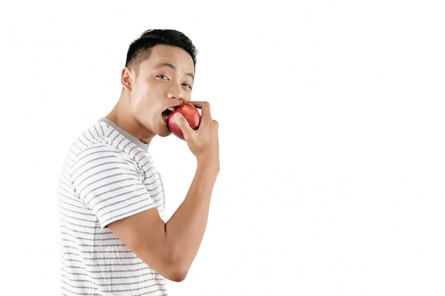 Young man biting apple