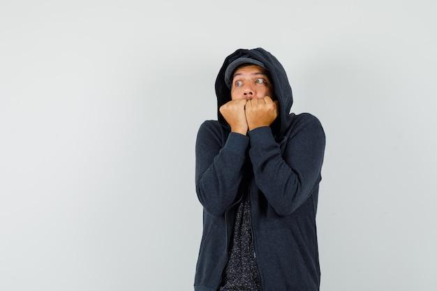 若い男は拳を噛み、tシャツ、ジャケット、キャップで冷たく感じ、謙虚に見えます。正面図。