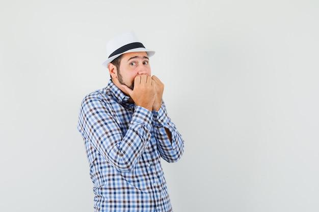 젊은 남자는 체크 셔츠, 모자에 감정적으로 주먹을 물고 무서워, 전면보기.