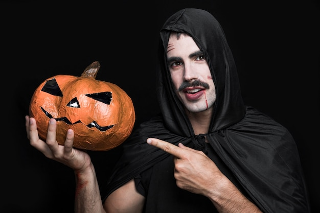Young man in black cloak pointing at halloween pumpkin