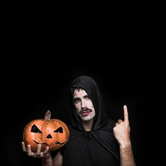 Young man in black cloak posing in studio with halloween pumpkin