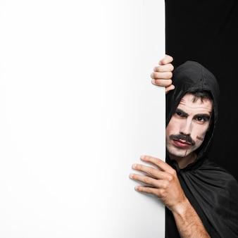 Young man in black cloak posing in studio