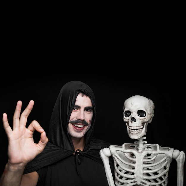 Young man in black cloak standing with skeleton and showing ok gesture