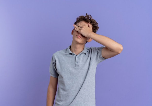 Young man in black glasses wearing grey polo shirt covering eyes with hand tired and bored standing over blue wall