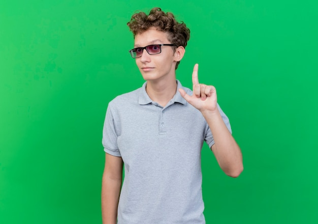 Young man in black glasses wearing grey polo shirt  happy and positive showing index finger having new idea standing over green wall