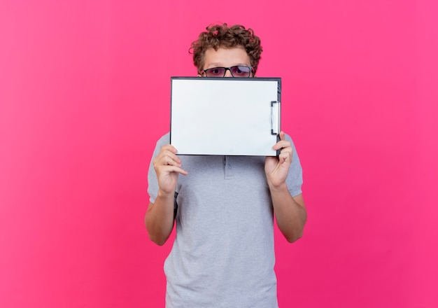 Young man in black glasses wearing grey polo shirt holding clipboard with blank pages hiding his face behind it peeking over standing over pink wall