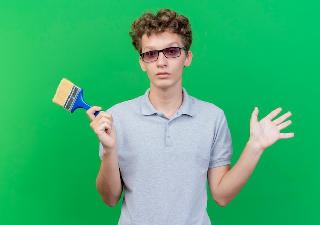 Young man in black glasses wearing grey polo shirt holding paint brush raising hand being confused standing over green wall