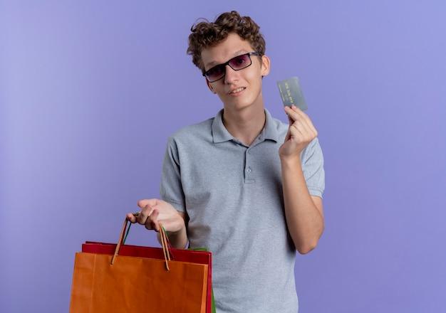 Giovane uomo con gli occhiali neri che indossa una polo grigia che tiene i sacchetti di carta e la carta di credito che sorride in piedi sopra la parete blu