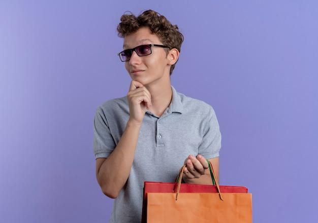 Giovane uomo con gli occhiali neri che indossa la maglietta polo grigia che tiene i sacchetti di carta che osserva da parte con ahnd sul mento pensando che sta sopra la parete blu