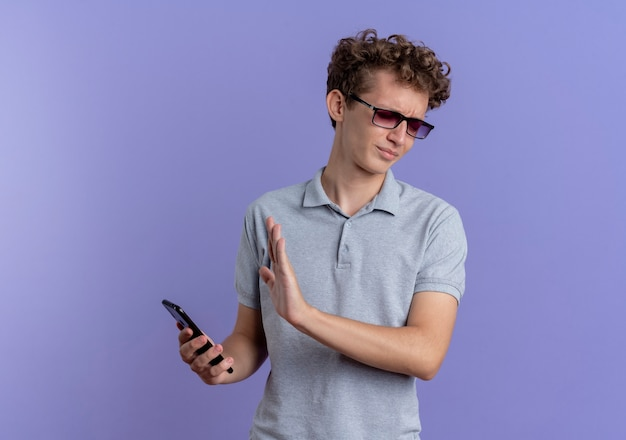 Young man in black glasses wearing grey polo shirt holding smartphone making defense gesture with hand over blue