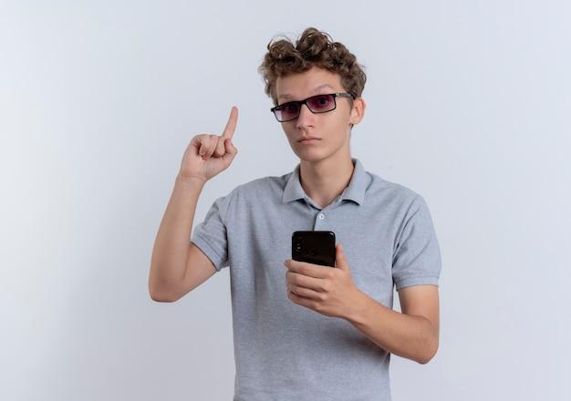 Giovane uomo con gli occhiali neri che indossa una polo grigia che tiene smartphone che mostra il dito indice che sembra sorpreso avendo nuova idea in piedi sopra il muro bianco