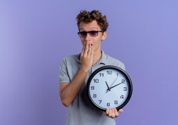 Giovane uomo con gli occhiali neri che indossa la maglietta polo grigia che tiene l'orologio da parete che sembra sorpreso e stupito in piedi sopra la parete blu
