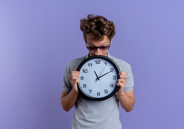 Giovane uomo con gli occhiali neri che indossa la maglietta polo grigia che tiene orologio da parete che sembra preoccupato in piedi sopra la parete blu