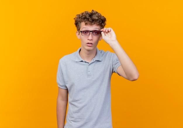 Giovane uomo con gli occhiali neri che indossa la maglietta polo grigia lookign alla telecamera concentrandosi duramente toccando i suoi occhiali su arancione