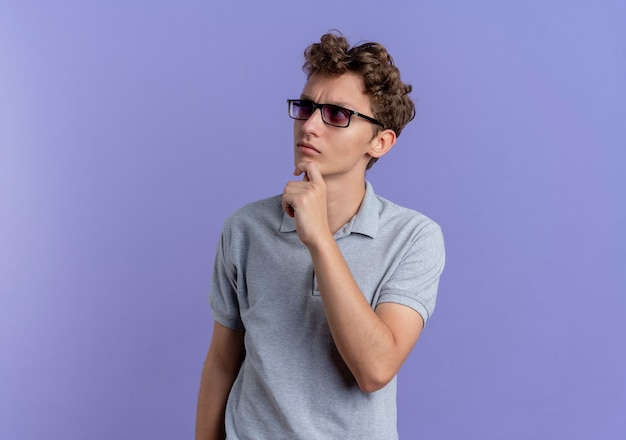Young man in black glasses wearing grey polo shirt looking aside puzzled standing over blue wall