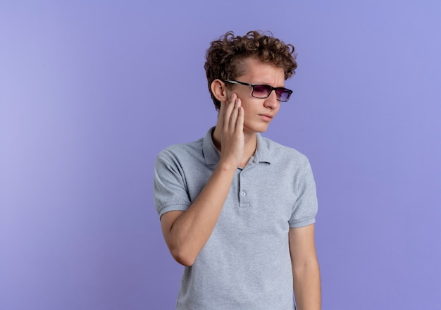 Young man in black glasses wearing grey polo shirt looking aside touching his cheek feeling toothache standing over blue wall