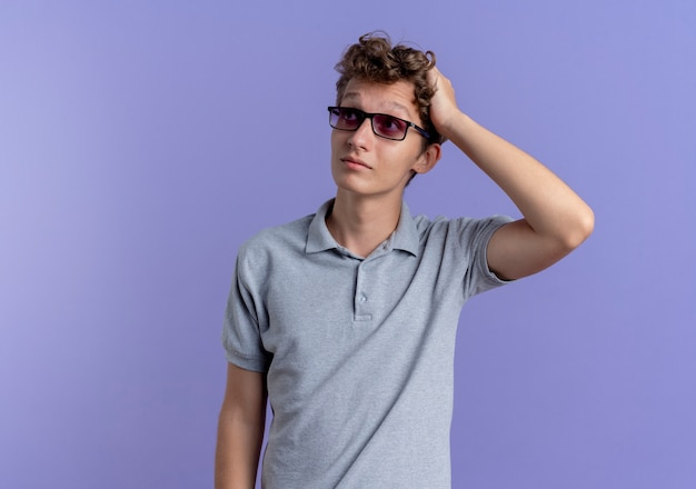 Young man in black glasses wearing grey polo shirt looking aside with hand on his head being confused standing over blue wall