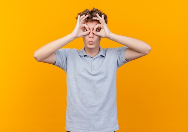 Young man in black glasses wearing grey polo shirt making binocular gesture with fingers looking through fingers over orange