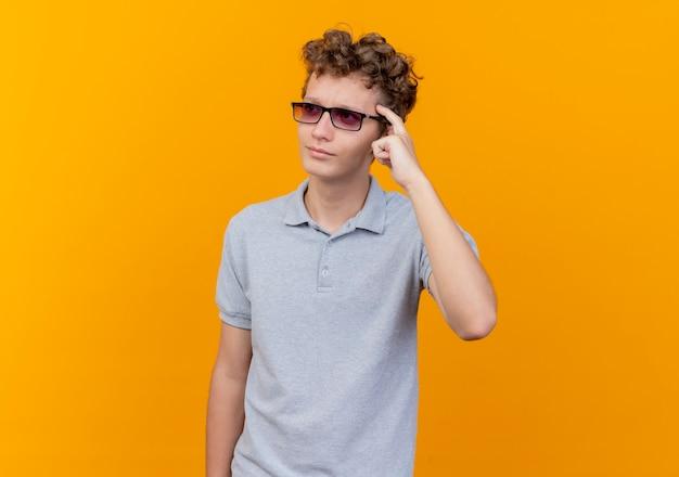 Giovane uomo con gli occhiali neri che indossa una polo grigia che punta alla tempia cercando di ricordare una cosa importante sull'arancio