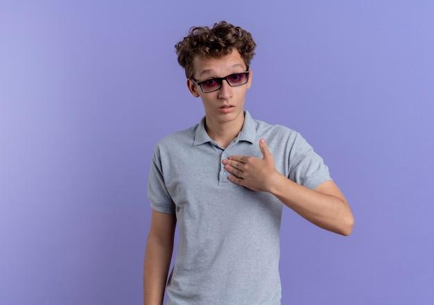 Giovane uomo con gli occhiali neri che indossa una polo grigia che punta a se stesso essendo confuso in piedi sopra il muro blu