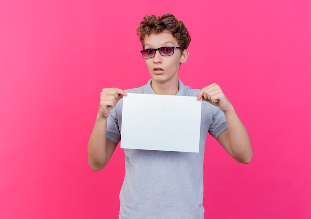 Giovane uomo con gli occhiali neri che indossa una polo grigia che mostra un foglio di carta bianco sorpreso in piedi sul muro rosa