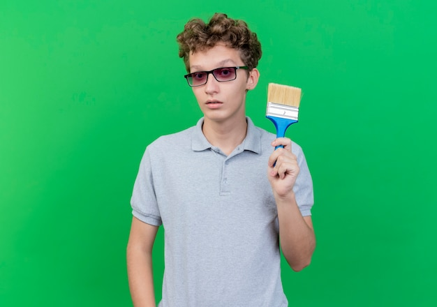 Young man in black glasses wearing grey polo shirt showing paint brush  with serious face standing over green wall