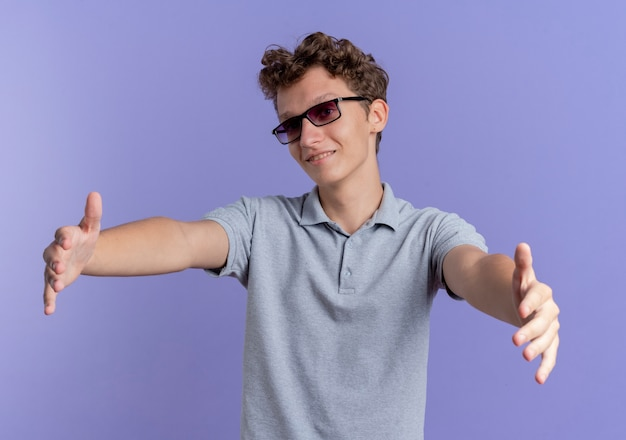 Giovane uomo con gli occhiali neri che indossa la maglietta polo grigia sorridente amichevole rendendo gesto di benvenuto ampia apertura mani in piedi sopra la parete blu