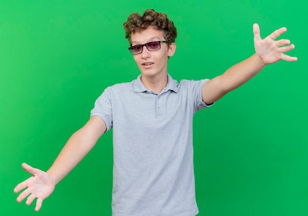 Giovane uomo con gli occhiali neri che indossa la maglietta polo grigia sorridente amichevole ampia apertura mani accoglienti in piedi sopra la parete verde