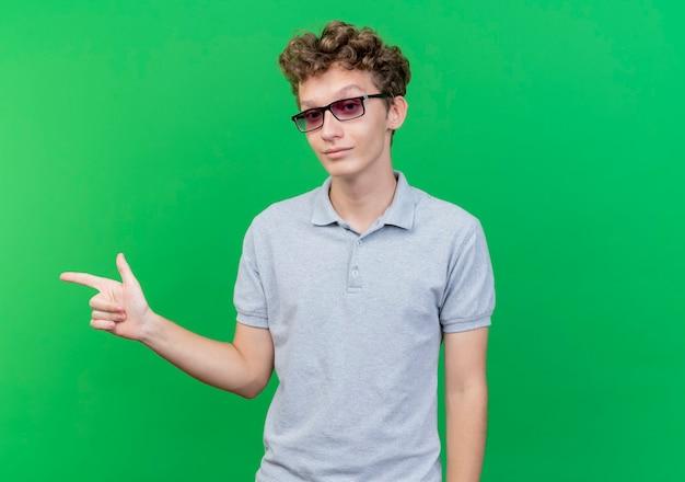 Giovane uomo con gli occhiali neri che indossa la maglietta polo grigia sorridente che punta con il dito indice a lato in piedi sopra la parete verde