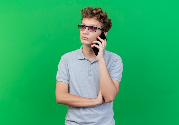 Giovane uomo con gli occhiali neri che indossa la maglietta polo grigia parlando al telefono cellulare guardando con faccia seria sul verde