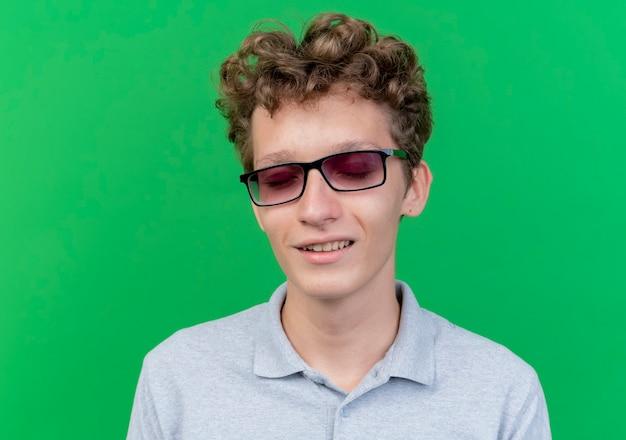 Giovane uomo con gli occhiali neri che indossa una polo grigia con gli occhi chiusi sorridendo allegramente in piedi sopra la parete verde