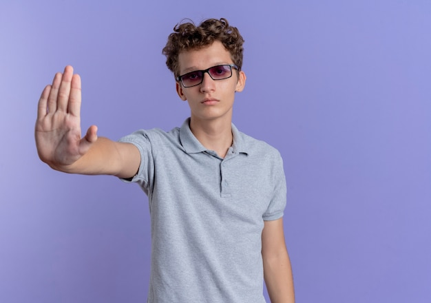 Young man in black glasses wearing grey polo shirt  with frowning face making stop gesture with hand standing over blue wall