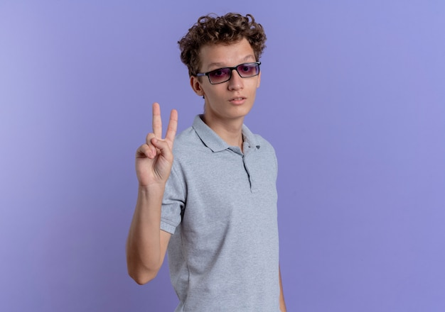 Young man in black glasses wearing grey polo shirt with seriosu face showing and pointing up with fingers number two over blue