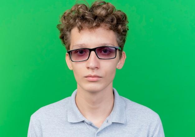 Giovane uomo con gli occhiali neri che indossa una polo grigia con la faccia seria sul verde
