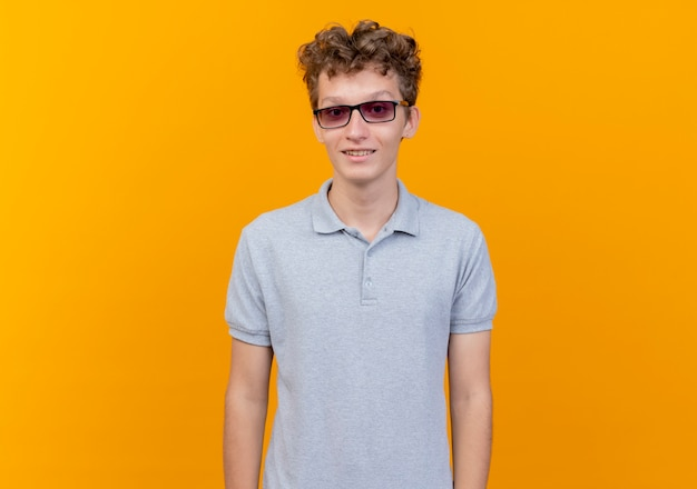 Giovane uomo con gli occhiali neri che indossa una polo grigia con il sorriso sul viso sopra l'arancio