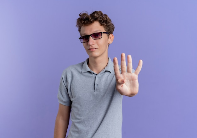 Young man in black glasses wearing grey polo shirt  with smile on face showing and pointing up with fingers number four standing over blue wall