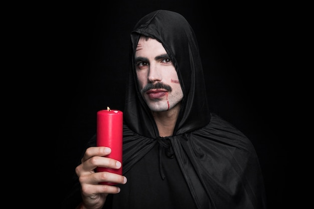 Young man in black halloween costume posing in studio with candle