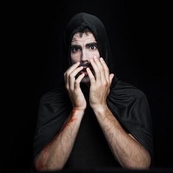 Young man in black halloween costume posing in studio