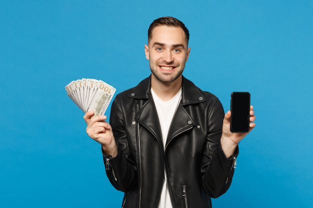 Young man in black jacket white t-shirt hold mobile phone empty screen for promotional content cash money isolated on blue wall background studio portrait. people lifestyle concept. mock up copy space