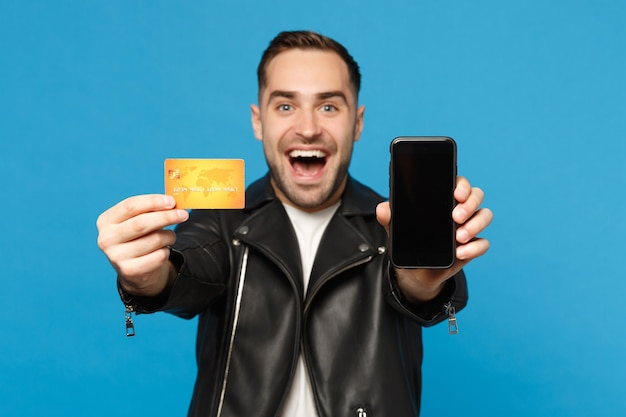 Young man in black jacket white t-shirt hold mobile phone empty screen for promotional content credit card isolated on blue wall background studio portrait. people lifestyle concept mock up copy space