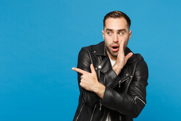 Young man in black jacket white t-shirt whispers gossip and tells secret with hand gesture, pointing index finger aside isolated on blue wall background. people lifestyle concept. mock up copy space.