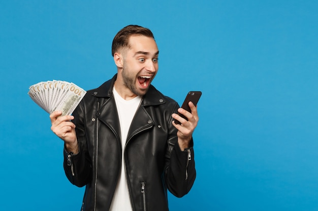 Young man in black leather jacket white t-shirt holding fan of cash money in dollar banknotes, cellphone isolated on blue wall background studio portrait. people lifestyle concept. mock up copy space.