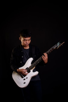 Young man in black leather jacket with electric guitar