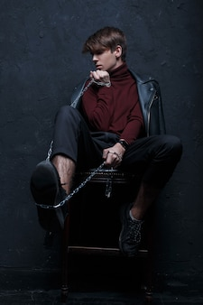 A young man in a black leather vintage jacket in a trendy burgundy golf in black pants and stylish sneakers sits on a wooden chair and holds a metal chain in the studio near the wall. fashionable guy
