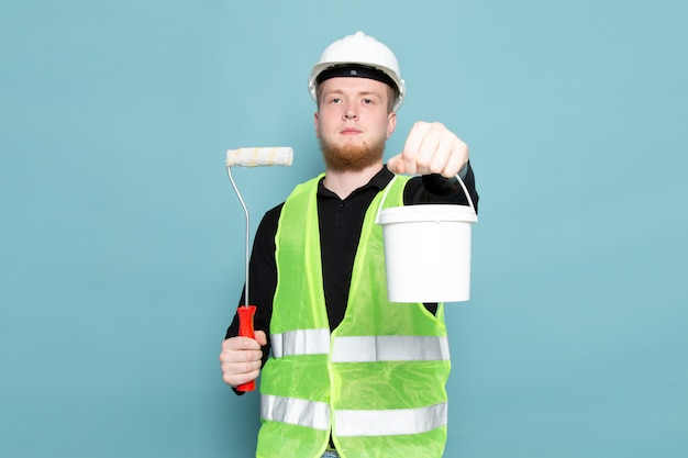 Young man in black shirt green and construction suit holding paint bucket