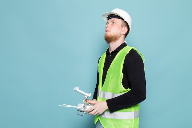 Young man in black shirt and green construction suit using remote control